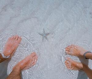 Füße im klaren Wasser am Meer neben Seestern